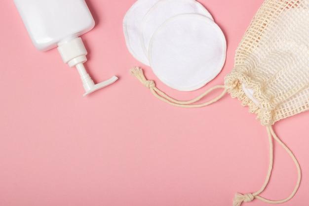 Tampons démaquillants réutilisables en coton dans un sac en tissu et nettoyant pour le visage et nettoyant sur fond rose. le concept d'écologie et de consommation consciente. tampons en coton réutilisables