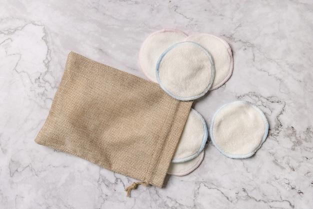Tampons démaquillants réutilisables écologiques dans un sac sur fond de marbre blanc