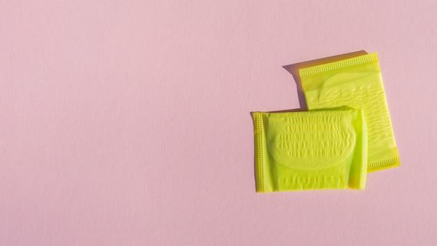 Tampons enveloppés jaunes avec fond d'espace de copie rose