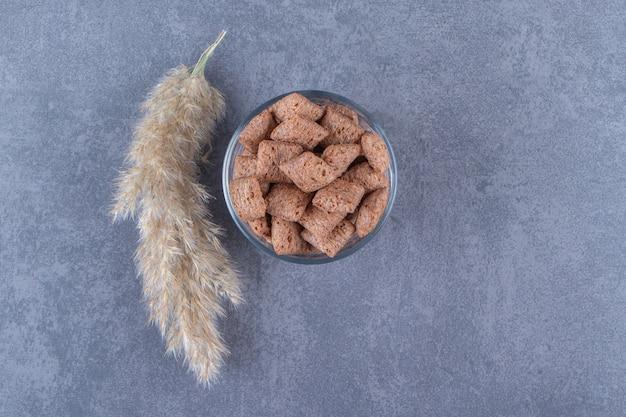 Tampons de maïs au chocolat dans un verre à côté de l'herbe de la pampa, sur fond bleu. photo de haute qualité