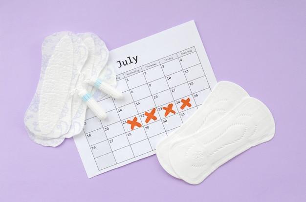 Tampons et tampons menstruels sur le calendrier de la période de menstruation à plat