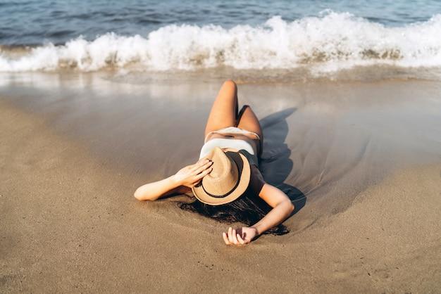 Tan fille en maillot de bain allongé sur la plage près de la mer avec un chapeau sur son visage.