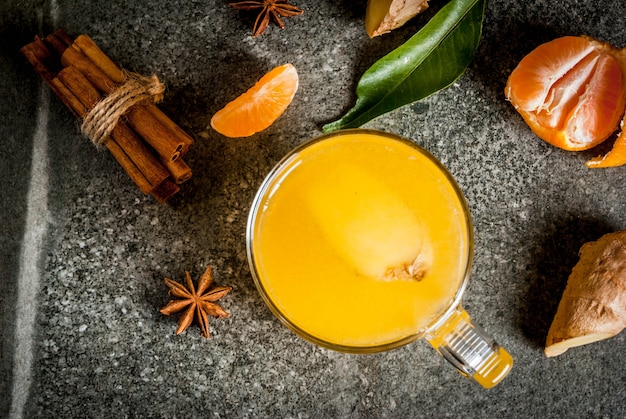 Tangerine ginger tea à la cannelle et à l'anis, avec des ingrédients, sur fond de pierre sombre, copie espace vue de dessus