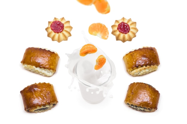 Tangerine tombant dans un verre de lait avec des éclaboussures autour desquelles sont de délicieux biscuits