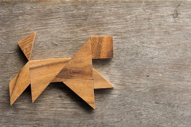 Tangram en bois en forme de chien en cours d'exécution sur le vieux fond de bois