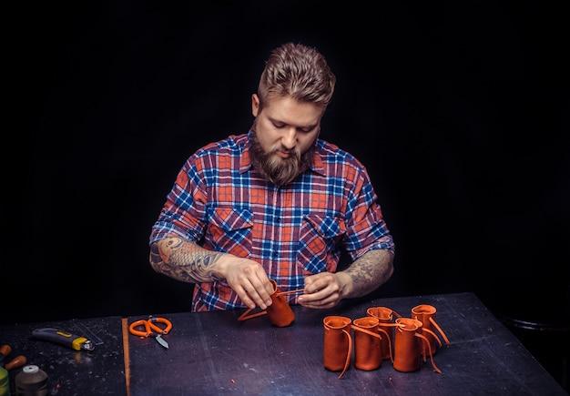 Tanner of leather travaille le cuir pour un nouveau produit dans l'atelier du cuir. / artisan travaillant comme artisan sur son lieu de travail.