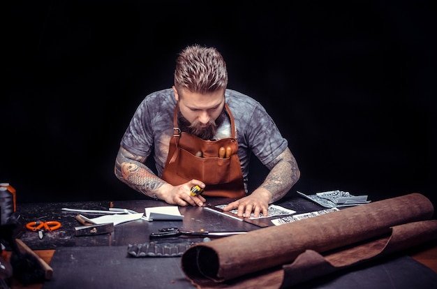 Tanner professionnel formant une nouvelle production de cuir./tanneur de cuir étant passionné par son entreprise dans son atelier.