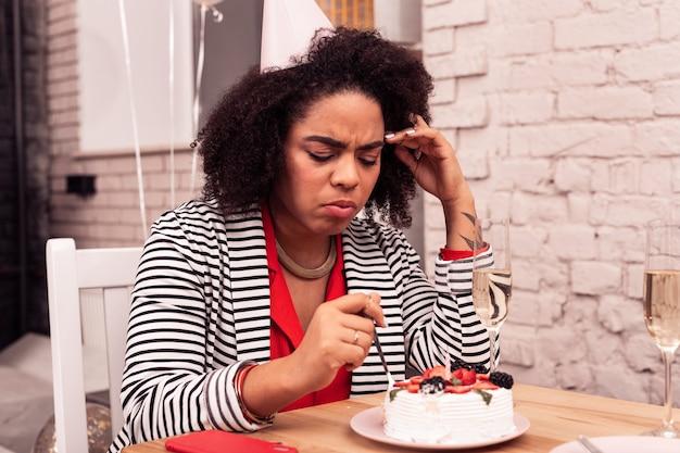 Tant de calories. malheureuse femme sombre regardant le gâteau tout en ne voulant pas le manger