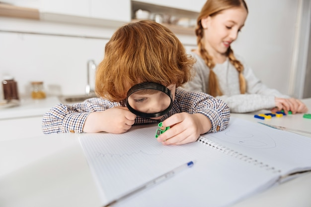 Tant de détails. gingembre animé concentré garçon à l'aide d'une grande lentille à l'un des nombres en plastique colorés sa sœur à l'aide de lui expliquer les mathématiques