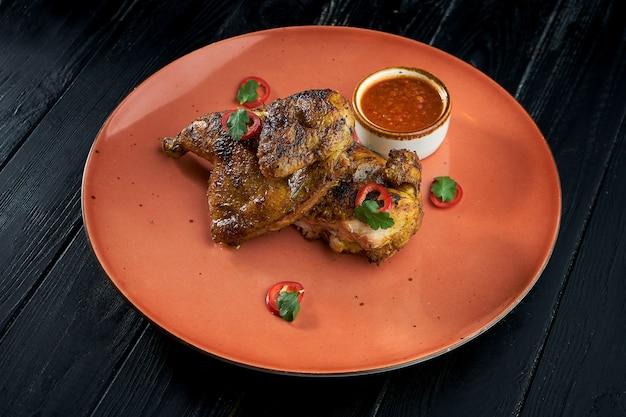 Tapaka de poulet sur une assiette, sur fond de bois. poulet grillé.