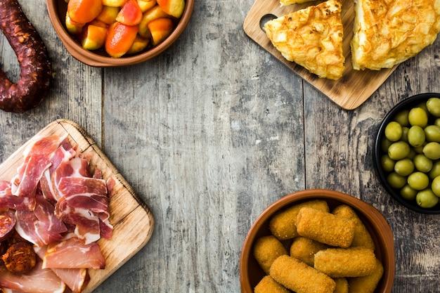 Tapas espagnoles traditionnelles. croquettes, olives, omelette, jambon et patatas bravas sur l'espace de copie de table en bois
