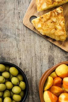 Tapas espagnoles traditionnelles. croquettes, olives, omelette, jambon et patatas bravas sur table en bois