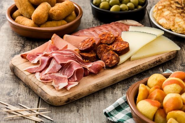 Tapas espagnoles traditionnelles croquettes, olives, omelette, jambon et patatas bravas sur table en bois