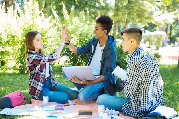 Tape m'en cinq. attrayante jeune femme donnant cinq à sa meilleure amie tout en étudiant ensemble dans le parc