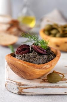 Tapenade noire ou tapas, plat traditionnel provençal ou trempette aux olives et basilic sur fond de table en bois ancien. mise au point sélective. vue de dessus