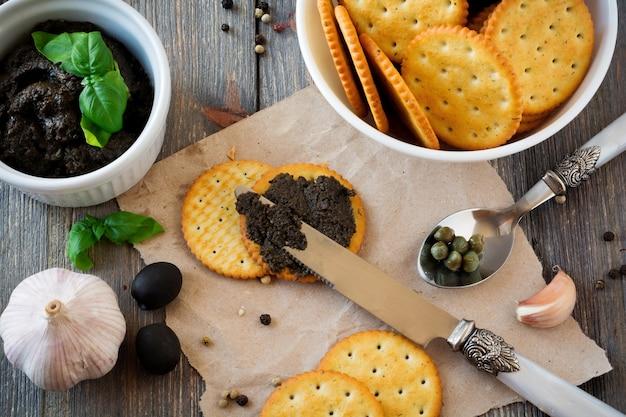 Tapenade, plat traditionnel provençal avec olives, craquelins et basilic sur une vieille surface de table en bois