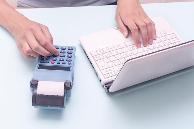 Taper à la main sur un ordinateur portable et une caisse enregistreuse sur fond bleu. vendeur entrant le montant sur la caisse enregistreuse dans le magasin de détail. concept d'interface de commerce électronique en ligne.