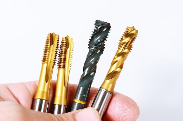 Tapez pour enfiler du métal sur une surface blanche. outil pour le traitement des métaux.