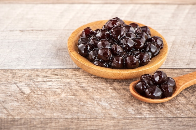 Tapioca pearl, garniture à bulles pour thé ou autre boisson, dans une tasse, placez sur une table en bois. copier l'espace