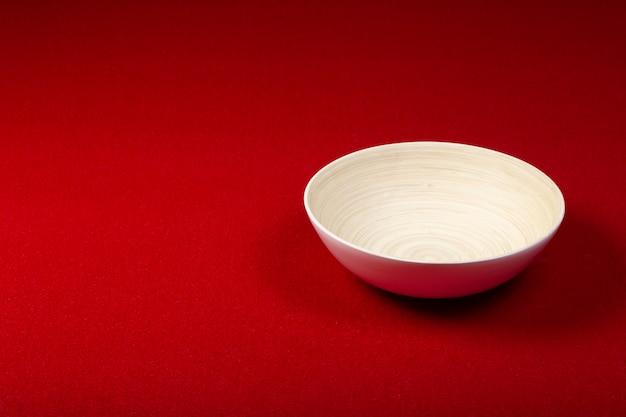 Tapis au fond. tapis de couleur rouge de la même couleur avec un bol en bois. conception et réalisation d'intérieur.