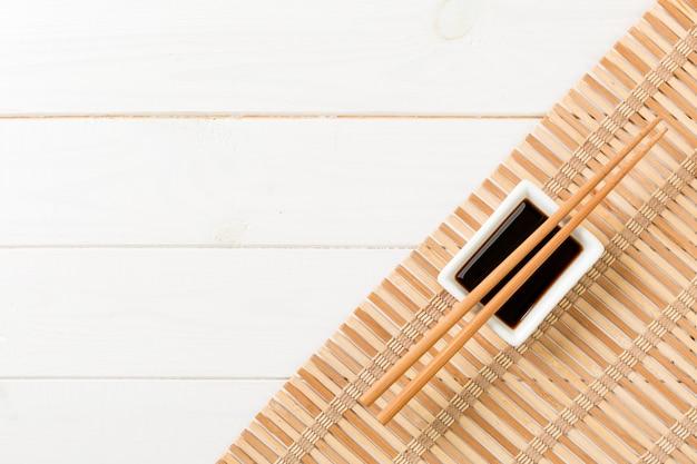 Tapis de bambou et sauce soja avec des baguettes de sushi sur une table en bois blanche.