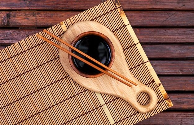 Tapis de bambou, sauce soja, baguettes sur table en bois foncé. vue de dessus avec espace copie