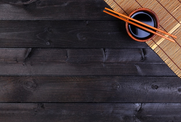 Tapis de bambou, sauce soja, baguettes sur table sombre