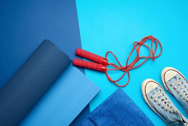 Tapis bleu torsadé, une paire de chaussures de sport bleues et une corde à sauter rouge