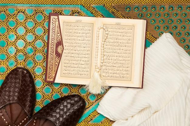 Tapis avec chaussures, serviette et livre sacré