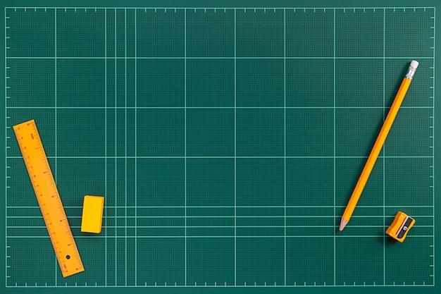 Tapis de coupe vert et papeterie orange