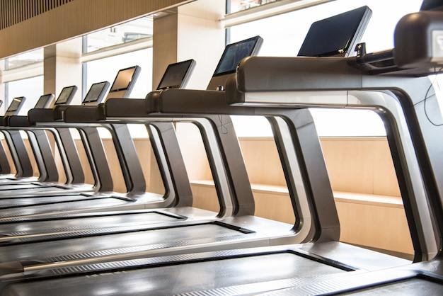 Tapis de course dans une salle de sport avec une belle lumière des machines de gym de fenêtre