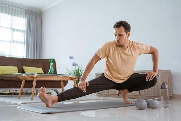 Tapis d'exercice pour jeune homme en forme asiatique tout en soulevant une jambe et en regardant vers la droite.