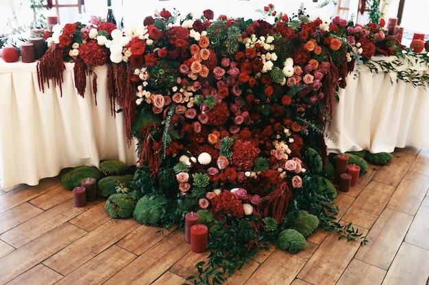 Tapis de fleurs rouges et de la mousse pend de la table du dîner