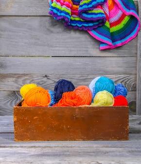 Tapis rayés colorés tricotés et boules de fil de laine brillant dans une boîte en bois sur fond de mur en bois ancien.