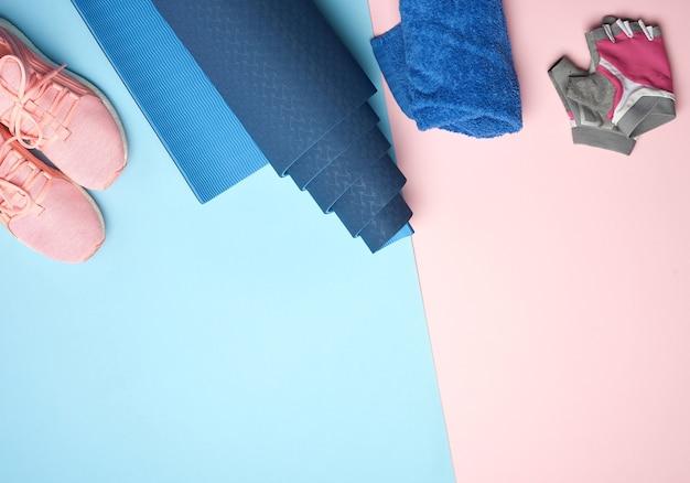 Tapis de sport enroulé, baskets roses, serviette et gants pour le sport