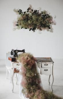 Un tapis vert est suspendu à la machine à coudre sur une table