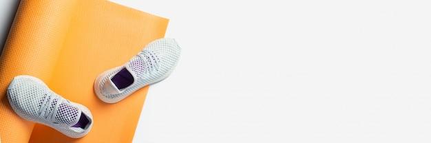 Tapis de yoga et baskets sur fond blanc. sport et alimentation. vue de dessus. bannière