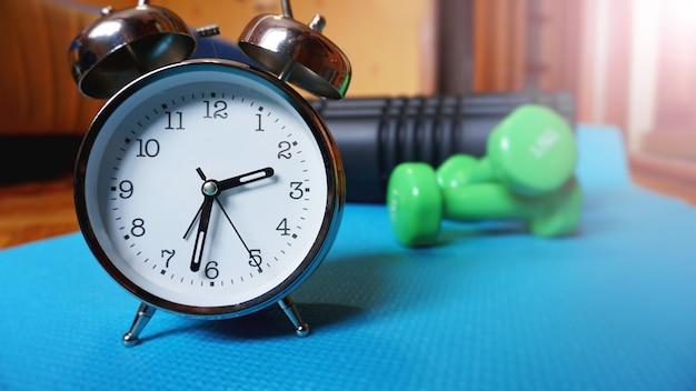 Tapis de yoga bleu, deux haltères, réveil, rouleau d'auto-massage - l'heure du sport à la maison