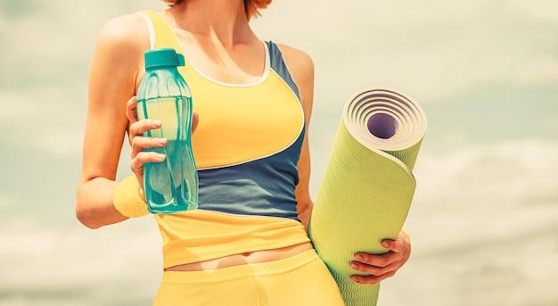 Tapis de yoga et bouteille d'eau. fille de remise en forme avec tapis de yoga.