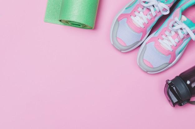 Tapis de yoga, chaussures de sport, bouteille d'eau sur rose