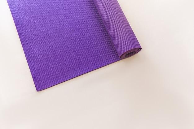 Tapis de yoga violet allongé sur le sol clair