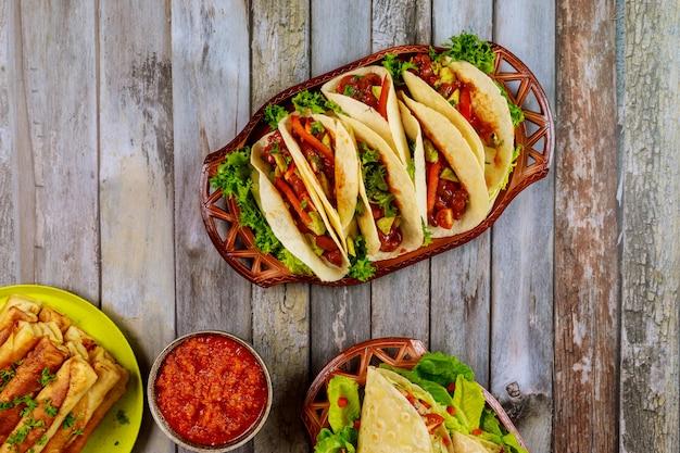 Taquitos, tortillas molles et salsa sur table en bois