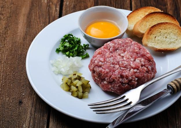 Tartare de bœuf frais avec œuf, concombre mariné et oignon.