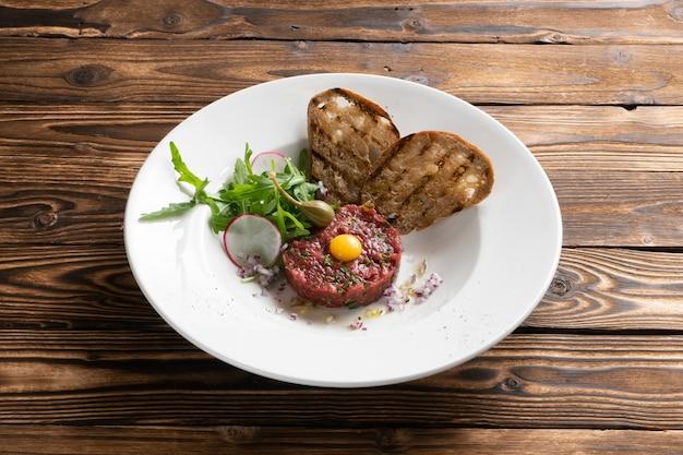 Tartare de bœuf mariné à l'oeuf de caille, salade de roquette, radis, câpres et ciabatta grillée