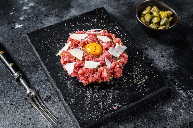 Tartare de bœuf avec un œuf de caille, câpres et parmesan. fond noir. vue de dessus.