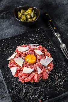 Tartare de bœuf avec un œuf de caille, câpres et parmesan.
