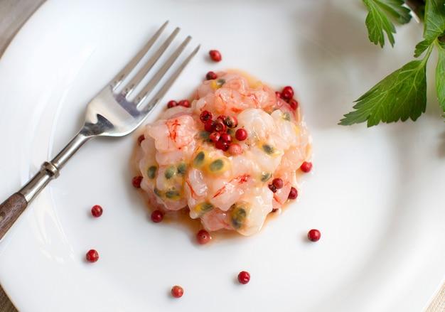 Tartare de crevettes crues aux fruits de la passion et poivre rose close up