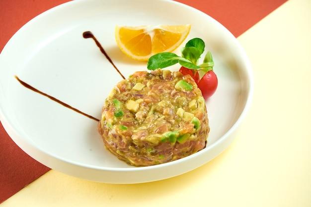Tartare de saumon à l'avocat et au citron dans une assiette blanche sur une surface colorée.