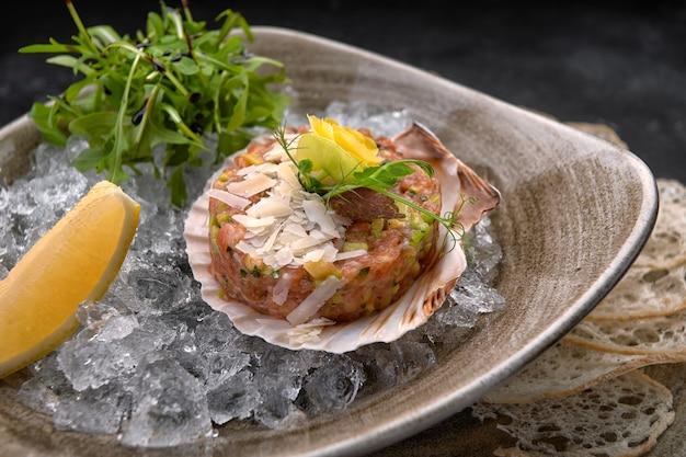 Tartare de saumon à l'avocat, chips de pain et citron, sur une assiette, sur un fond sombre, sur un crash de glace