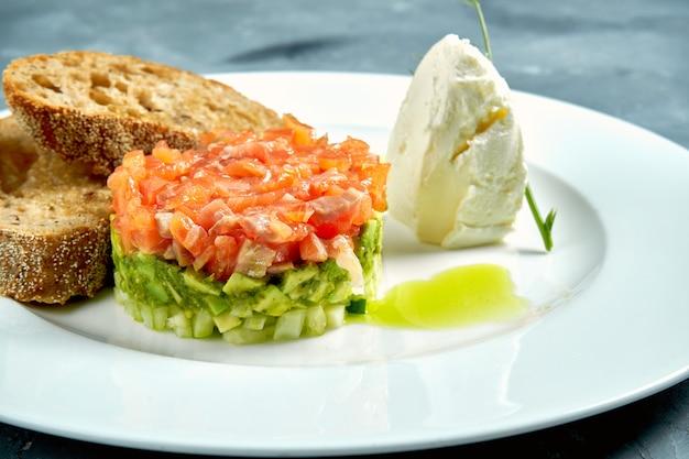 Tartare de saumon et d'avocat, croûtons dans une assiette blanche sur béton